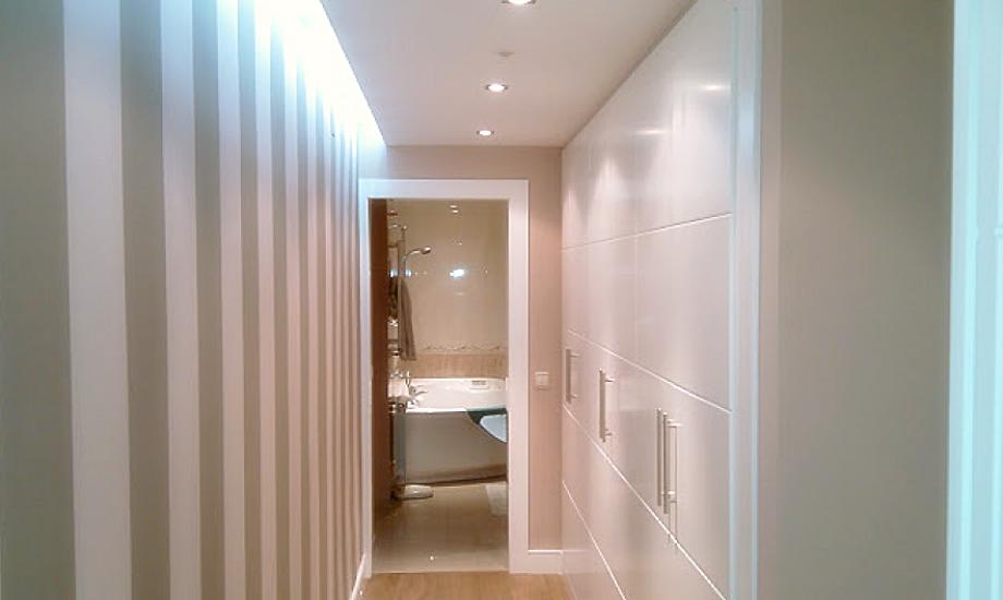 En la imágen puede observar un pasillo con armarios y la parte iluminada es la pared decorada con papel.